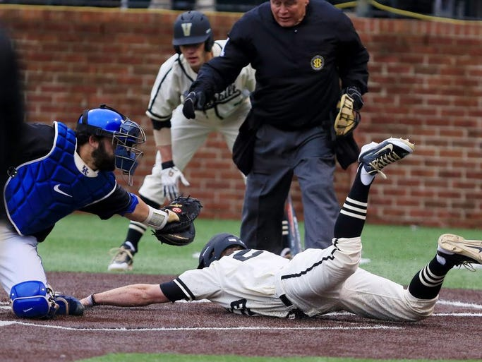 Vanderbilt's Will Cooper dives under the glove of Kentucky catcher Michael Thomas and is safe at home Saturday. Vanderbilt won 9-3 to even the weekend series.