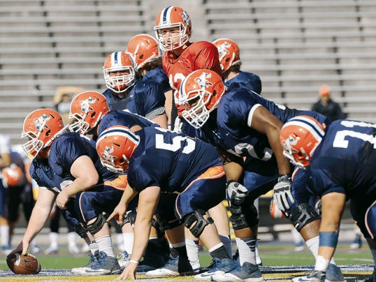 UTEP quarterback Ryan Metz, top center in red,  calls out signals at the line of scrimmage.