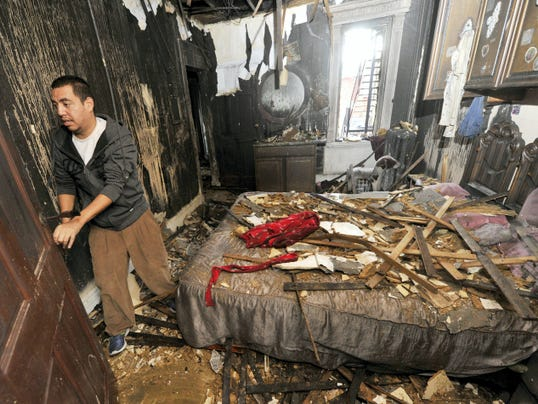 Joel Ruelas, owner of the home along the 300 block of East Poplar Street in York city, forces a bedroom door open so he can check his closets for clothes Thursday.