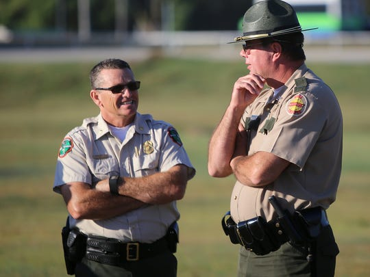 Tennessee Wildlife Resources Agency Maj. Brian Thompson and Tennessee Highway Patrol Lt. Brad Wilbanks chat before an announcement about Beyond the Badge at the Jackson Fairgrounds.