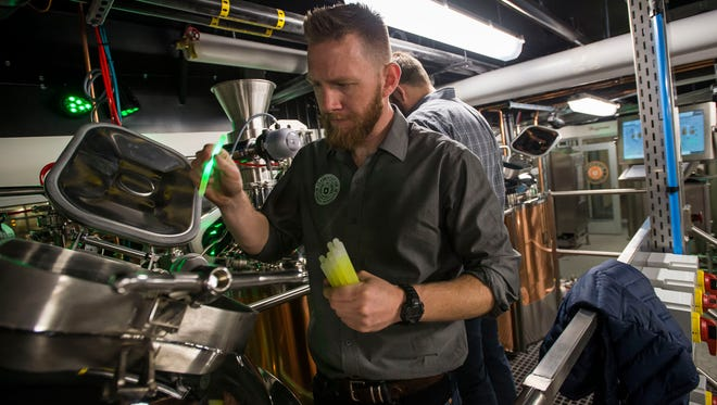 Associate director of CSU fermentation science and technology program Jeff Callaway tosses glow sticks into the fermentors before the unveiling of CSU's new student-run brewery on Monday, April 9, 2018, at the Ramskeller Pub & Grub in the Lory Student Center in Fort Collins, Colo.