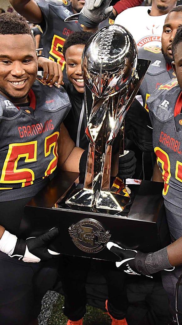 Grambling players hoist up the Bayou Classic trophy