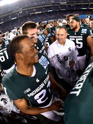 Cam Chambers (21) grins while celebrating with Mark Dantonio after Thursday night's victory.