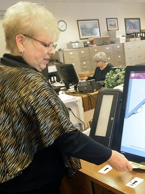 Clerk/Treasurer Nikki Bryan puts a voter card in one of the county's new voting machines.