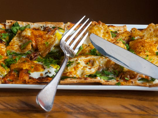 Somewhere Restaurant and Bar's breakfast flatbread is like a breakfast pizza. Its made with ricotta sauce (lemon and parmesan cheese,) fresh spinach, fresh mozzarella, chopped bacon, egg and basil.