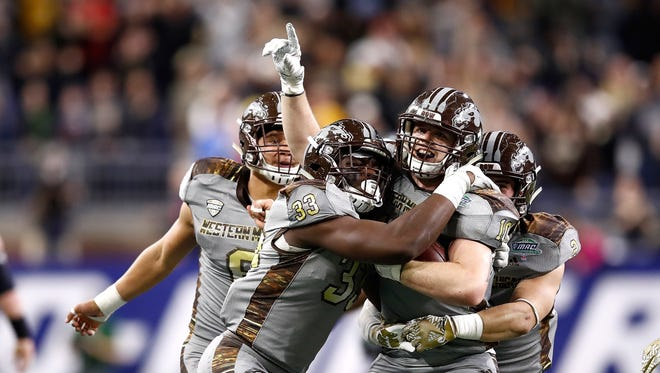 Robert Spillane (10) of Western Michigan celebrates his fourth-quarter interception with Asantay Brown (6), Eric Assoua (33) and Justin Tranquill (2) while playing Ohio during the Mid-American Conference Championship on Dec. 2 at Ford Field in Detroit.