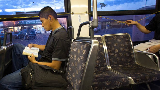 Gerson Gonzalez reads during his city bus ride to North High School.
