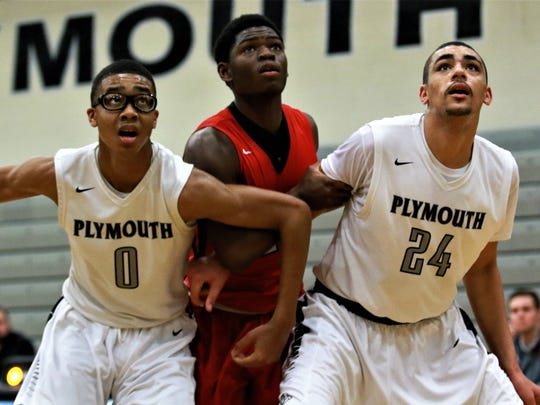 Keeping their focus on the basketball are Plymouth's Anthony Crump (0), Tariq Woody (24) and Canton's Noah Brown.