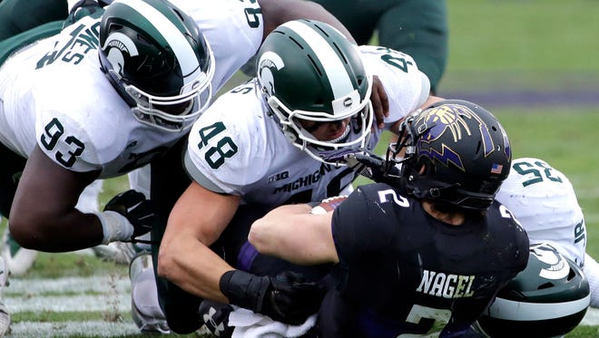 Michigan State defensive tackle Naquan Jones (93), defensive end Kenny Willekes (48) and linebacker Joe Bachie (35) tackle Northwestern wide receiver Flynn Angel (2) during the first half of an NCAA college football game in Evanston, Ill., Saturday, Oct. 28, 2017.