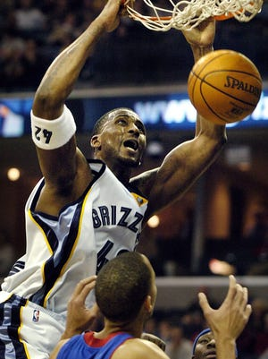 The Grizzlies #42 Lorenzen Wright slams home a dunk over  the Pistons' Tayshaun Prince during their game Saturday at the Fed Ex Forum.