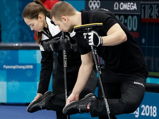 Russian atheletes Anastasia Bryzgalova,left, and Aleksandr Krushelnitckii check their shoes before the start of their mixed doubles curling match against Norway at the 2018 Winter Olympics in Gangneung, South Korea, Tuesday, Feb. 13, 2018. The Russian athletes won bronze medal. (AP Photo/Aaron Favila)