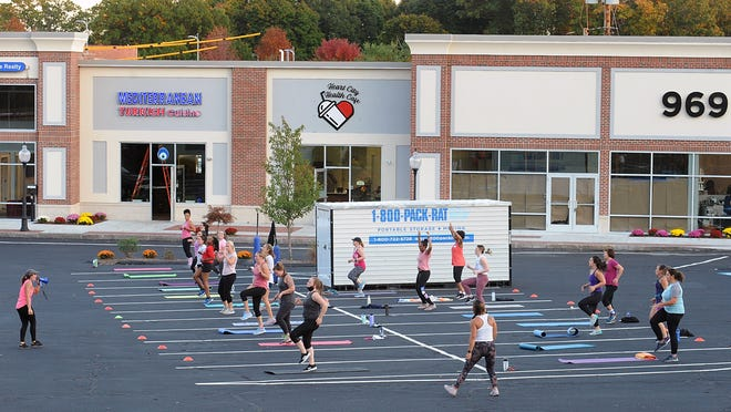 Burn Boot Camp Head Trainer Brittany Clark, left, leads a 45-minute, high-intensity workout in the parking lot of the newly rebuilt Old Path Village Wednesday evening.