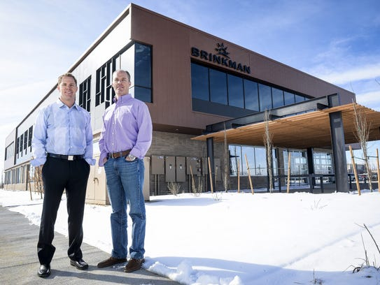 Kevin and Paul Brinkman stand outside the headquarters