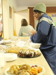 A volunteer dishes out deserts at the Otero County Hunger Coalition Thanksgiving meal Thursday afternoon.