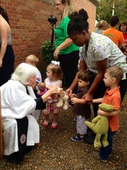 The Rev. Elizabeth Ratcliff performs the sign of the cross over a stuffed dog toy of Parker Marcase, 2, at St. James Episcopal Day School's annual animal blessing in honor of the feast day of St. Francis of Assisi on Friday. Parker is the son of John and Monica Marcase.