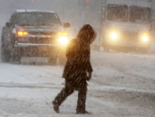 A pedestrian fights the wind blown snow while crossing