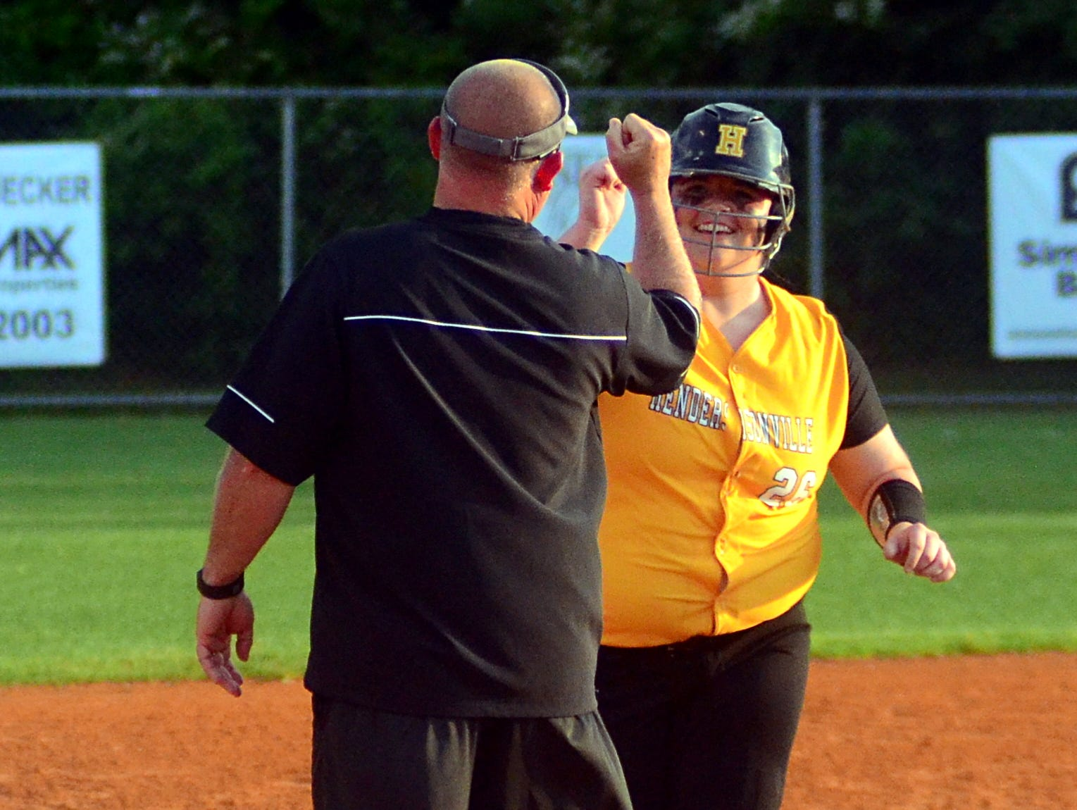 Hendersonville High senior Carley Carlisle is congratulated by head coach Jeff Serbin after her second home run in Tuesday's 5-3 victory over Lebanon in the District 9-AAA Tournament winners bracket semifinals.