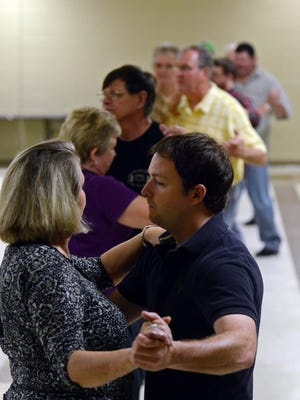 Attendees practice dance moves on a Tuesday night during ballroom dance lessons at the Sigler Community Center.