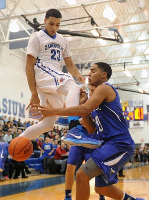 Cambridge's Maurice Lathan knocks the ball away from Zanesville's Malik Bocook during Friday night's game. Cambridge edged the Blue Devils, 51-50, in overtime for a East Central Ohio League victory.