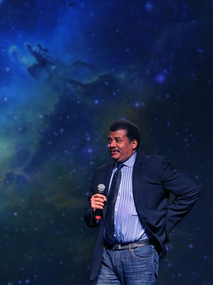 """Astrophysicist Neil deGrasse Tyson, host of Fox's """"Cosmos: A Spacetime Odyssey"""" mini-series, speaks to a crowd of 4,000 at the University of Indianapolis' Nicoson Arena Hall on Wednesday, October 22, 2014."""