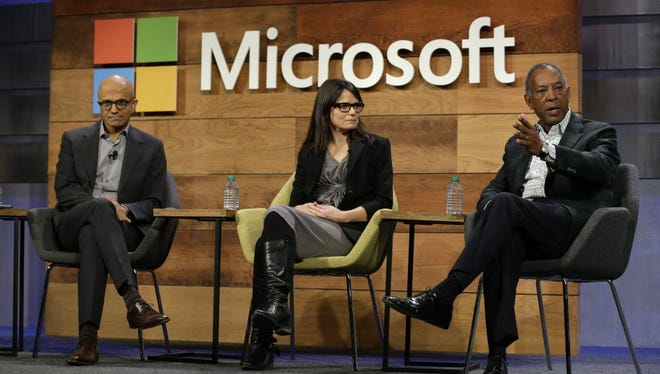 Microsoft board chairman John Thompson, right, addresses company shareholders at an annual meeting Wednesday. At left is CEO Satya Nadella, and in the center is CFO Amy Hood.