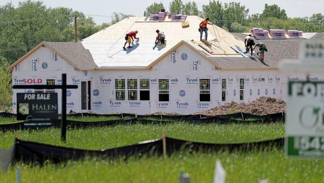 Crews work on a house being built in Brookdale Estates in Menomonee Falls.
