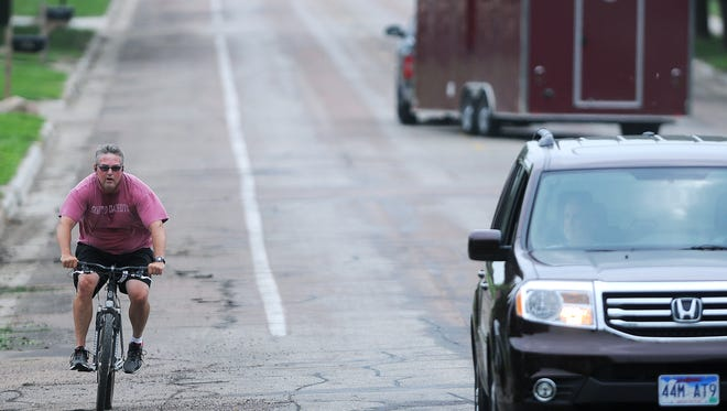 """Sam Leinen, of Sioux Falls, rides a bicycle North on Bahnson Avenue near its intersection with 36th Street in a shared parking and bicycle lane on Thursday, July 2, 2015, in Sioux Falls. """"I love having these lanes,"""" Leinen said."""