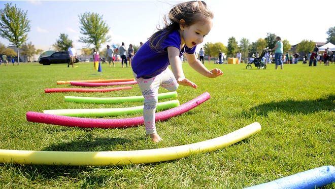 Emma Rangel takes a tumble at the end of the kids obstacle course set up at the St. Cloud Area Family YMCA fundraising event for the new community and aquatics center on Saturday at Whitney Park.