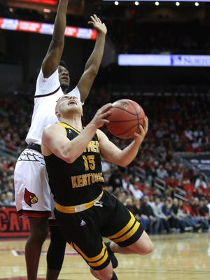 Northern Kentucky's Tyler Sharpe is tripped by Louisville's Darius Perry during first quarter action in the NIT. March 13, 2018.