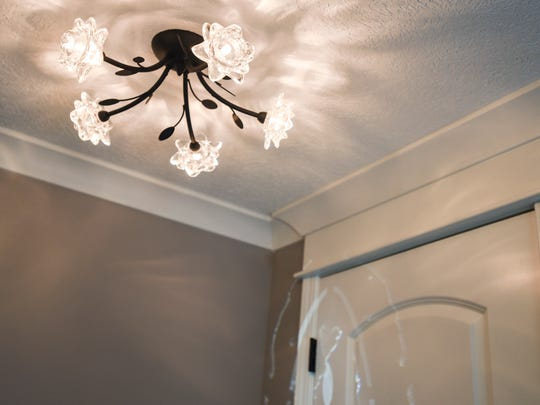 A detail of the crown molding and entryway lamp in