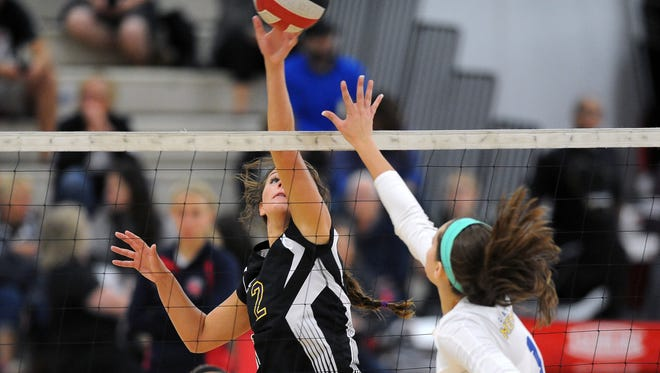 Oconomowoc's Amanda Garvens, left, hits the ball over the net against Catholic Memorial''s Kaitlyn Zingsheim during a semifinal volleyball match at the Homestead Joust girls volleyball tournament on at Homestead High School.