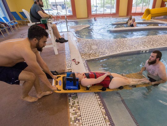 Joshua Apodaca, left, and Chris Behrems, right, pull fellow lifeguard Ashley Kulek out of the pool with the assistance of back board during a demonstration at the Las Cruces Regional Aquatic Center.