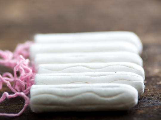 Clean white tampons lying on wooden surface.