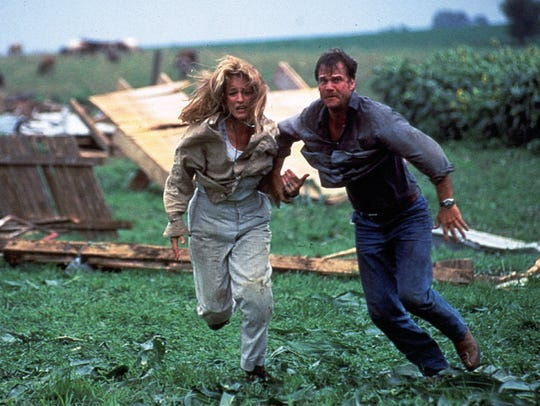 "Tornado-chasers Helen Hunt (left) and Bill Paxton make a run for it in ""Twister."""