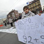 """A Bosnian boy holds a placard reading """"Europe, You Owe Us, Dont You Remember 92-95 (referring to the war),"""" while citizen rights activists gather in front of Bosnia and Herzegovina's presidency building to block traffic at one of the busiest intersections in  Sarajevo on Feb. 21, 2014."""