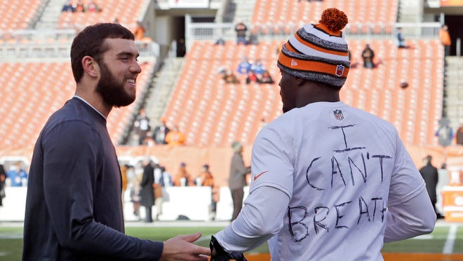 Indianapolis Colts quarterback Andrew Luck, left, talks with Cleveland Browns cornerback Johnson Bademosi before their game.