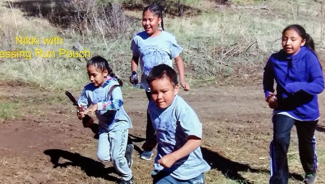 Mrs. Helmke's first grade students Nikki Torres and Esham Bigmouth-Hill, of Mescalero Apache School, carry the Blessing Run Pouch to the next marker.  Fourth grade students MaKayla Rocha and Shaidyn LaPaz assist the runners.