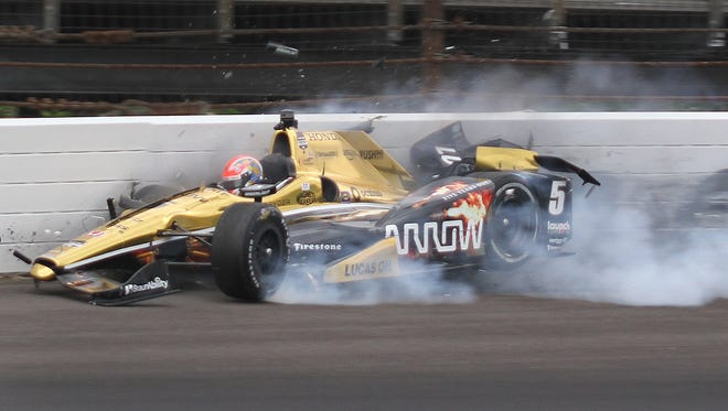 Schmidt Peterson Motorsports driver James Hinchcliffe (5) hits the wall coming out of turn 3 during practice for the 99th Indianapolis 500 Monday, May 18, 2015, morning at the Indianapolis Motor Speedway.