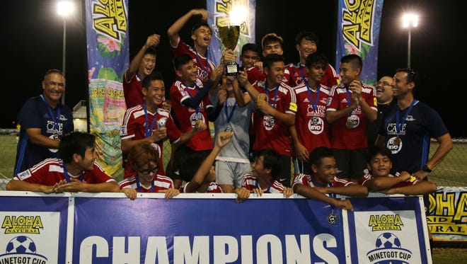 Wings Red proudly hoist the U15 Division championship trophy of the Aloha Maid Minetgot Cup Elite Youth Soccer League Saturday at the Guam Football Association National Training Center. Wings Red defeated the ASC Trust Islanders 8-4 in the final.