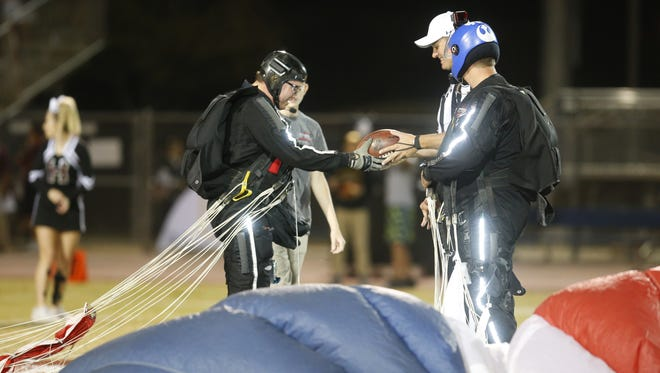 Carl Chitim, left, and Jeff Agard, right,  from Ariel Extreme hand over the game ball after parachuting in for the state football quarterfinal playoff at Perry High on October 20, 2017. #hsfb Perry vs. Hamilton