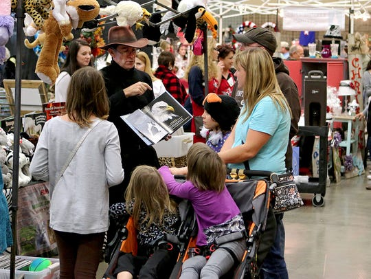 A vendor shows a book to a group of customers Saturday