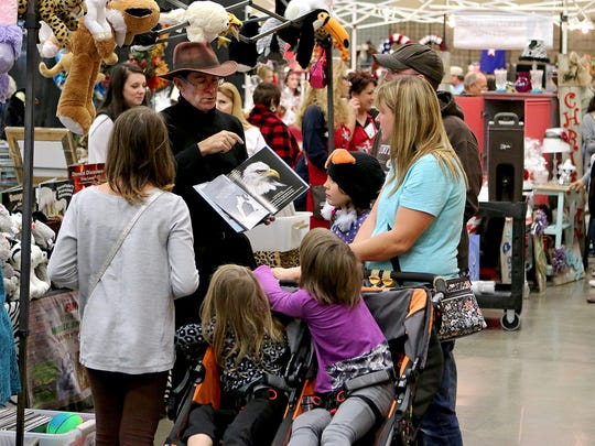A vendor shows a book to a group of customers Saturday afternoon during Hanger Holiday at the Multipurpose Events Center.