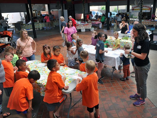 Children and parents listen as Jessica Bachman of the Wichita Falls Area Food Bank, right, tells them about the importance of eating healthy snacks. The hands-on activity included kids making their own veggie wraps with fresh ingredients.