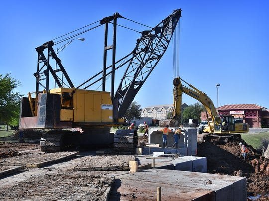 A crane lowers a section of concrete culvert into