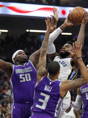 Grizzlies guard Tyreke Evans (12) drives to the basket as Kings forward Zach Randolph (50) and guard George Hill (3) defend during the first half Sunday.