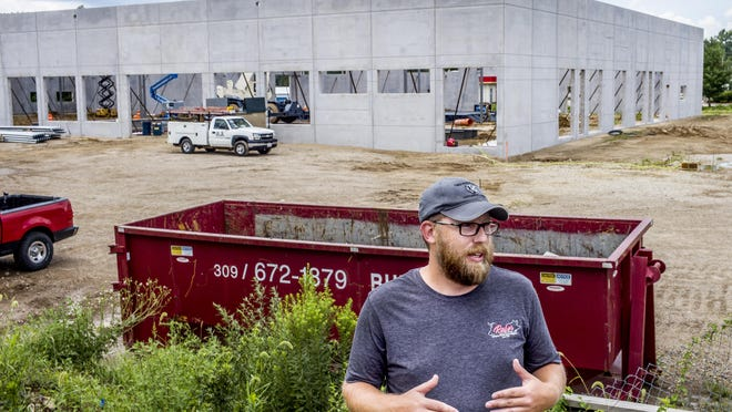 Raber Packing Co. owner Buddy Courdt talks Wednesday about the ongoing construction of the company's new facility, in background, along Farmington Road in West Peoria. A fire in 2018 destroyed the original facility.