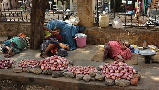 Indian vendors selling onions rest on a sidewalk under the shade of a tree on a hot summer day in Hyderabad, India, Monday, May 25, 2015. Hundreds of people have died since mid-April in a heat wave sweeping two southeast Indian states, Andhra Pradesh and Telangana, officials said Saturday. (AP Photo/Mahesh Kumar A.)