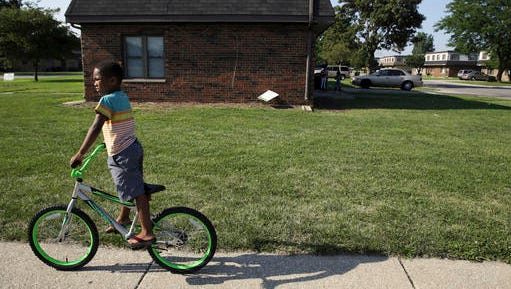 FILE In this Wednesday, Aug. 3, 2016 file photo, a child rides his bicycle past the West Calumet Housing Complex in East Chicago, Ind. The mayor of this industrial town ordered the evacuation of the 40-year-old public housing complex this summer because of severe lead contamination, forcing more than 1,000 people from their homes. (Jonathan Miano/The Times via AP)