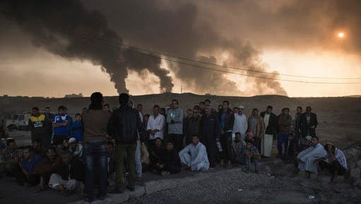 Men are held by Iraqi national security agents, to be interrogated at a checkpoint, as oil fields burn in Qayara, south of Mosul, Iraq, Saturday, Nov. 5, 2016. Islamic State fighters launch counterattacks in the thin strip of territory Iraqi special forces have recaptured in eastern Mosul, highlighting the challenges ahead as the battle moves into more densely populated neighborhoods where coalition air power must be used more selectively.