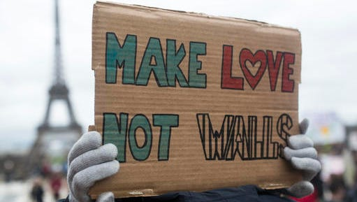 """A woman holds a banner reading """" Make love not walls"""" during a gathering to protest U.S. President Donald Trump's recent travel ban to the U.S. at Trocadero Plaza next to the Eiffel Tower in Paris, Saturday, Feb. 4, 2017. People gathered to protest Trump's executive order temporarily banning immigrants from seven Muslim-majority countries from entering the U.S. and suspending the nation's refugee program."""